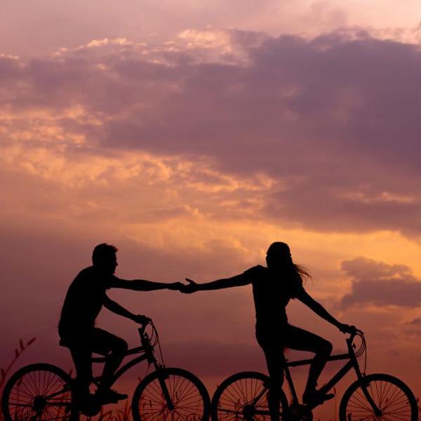 silhouette van twee fietsers tegen achtergrond met zonsondergang