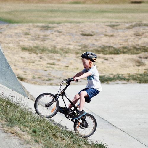 jongetje met helm op fiets in skatepark