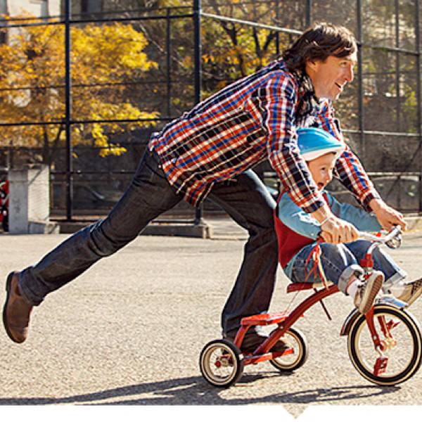 Vader leert kindje fietsen op driewieler
