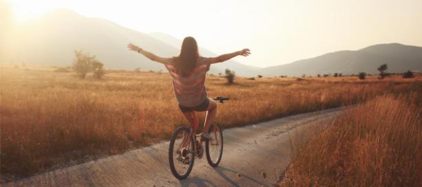 meisje fiets met armen gespreid met losse handen