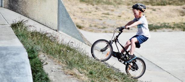jongetje fietst tegen helling op in skatepark